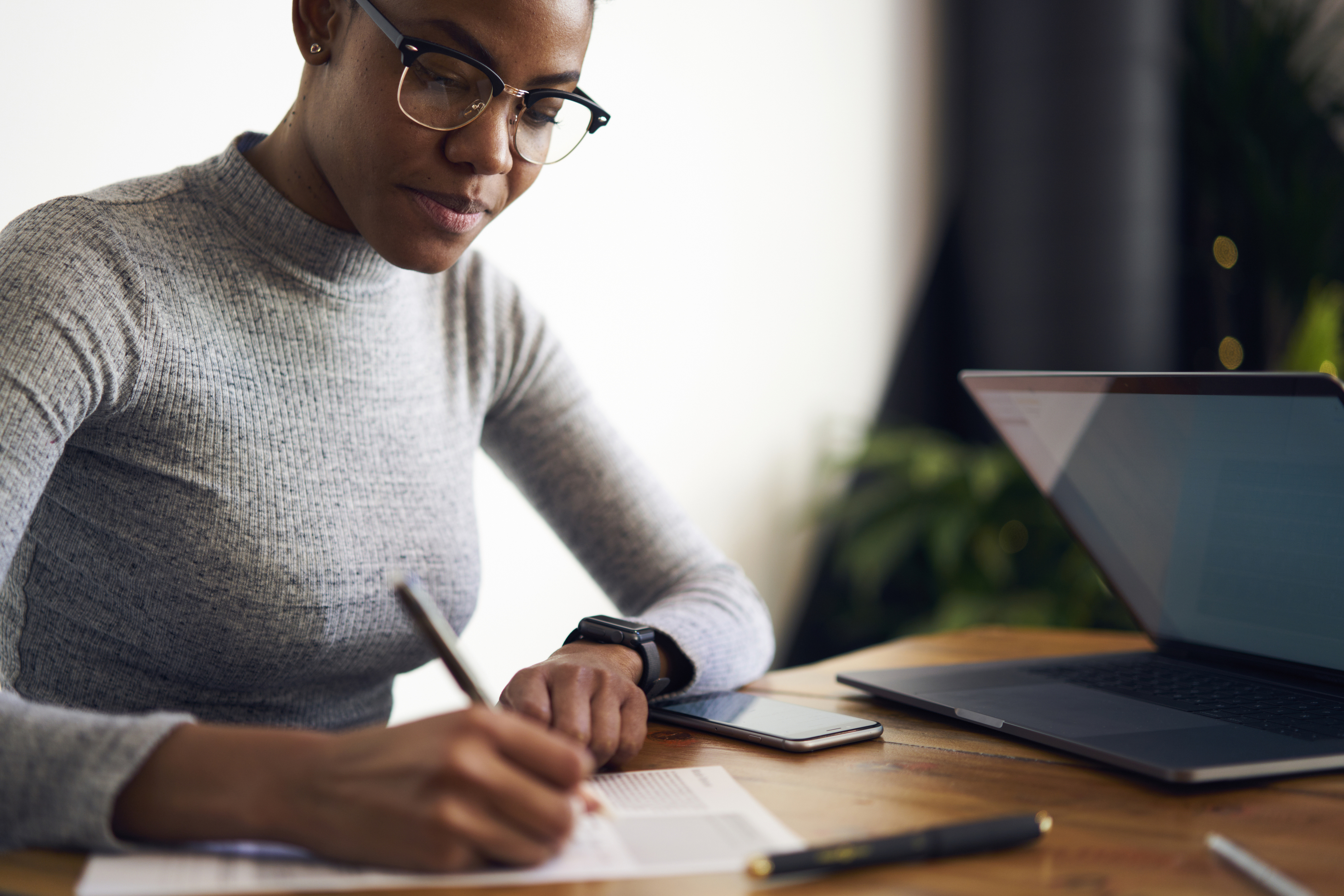 Experienced afro american female owner of business signing contract with corporation for making rebranding campaign to attract customers choosing best professional experts in online database